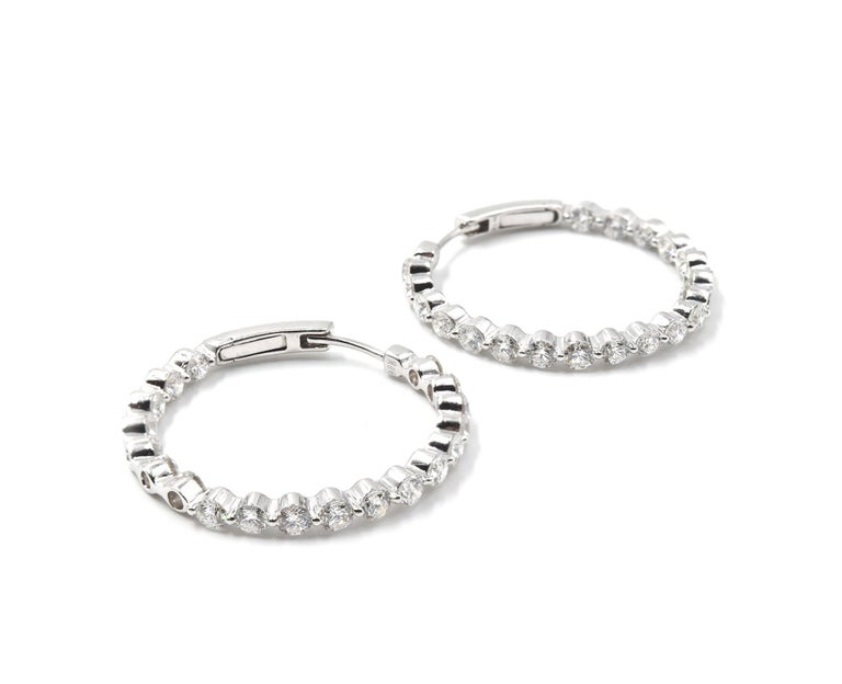 Designer: custom design Material: 18k white gold Diamonds: 38 round brilliant cut diamonds = 3.96 carat total weight Color: G Clarity: SI1 Dimensions: each hoop is 1 1/4-inch diameter Weight: 8.64 grams