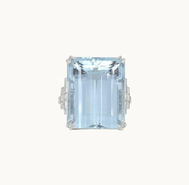 A large and very chic aquamarine and diamond platinum cocktail ring from circa the 2000s.  This beautiful ring features an emerald cut 39.78 carat aquamarine with 18 square cut diamonds on the sides, which total approximately 0.80 carats.