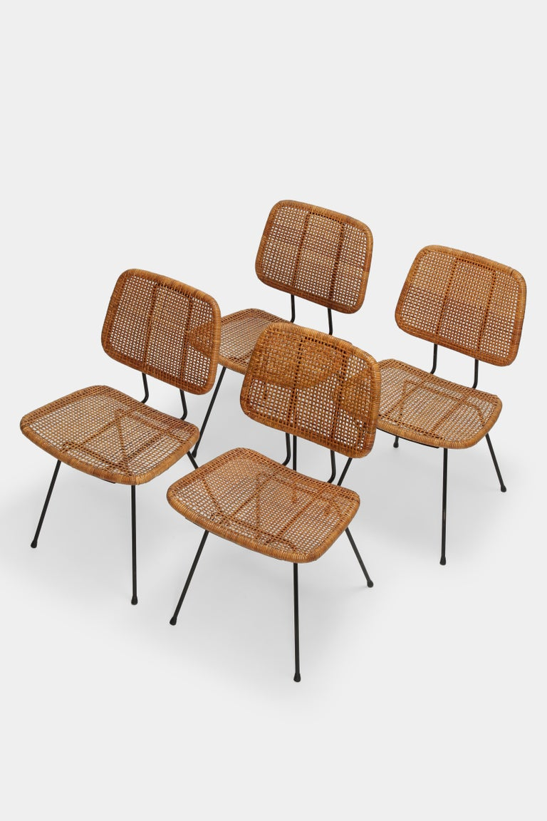 4 Dirk van Sliedregt Chairs 550 designed in the 1950s and manufactured by Rohé Noordwolde in the Netherlands. High quality wickerwork seat and backrest with a black lacquered metal base. Partly restored recently and in a great condition with a