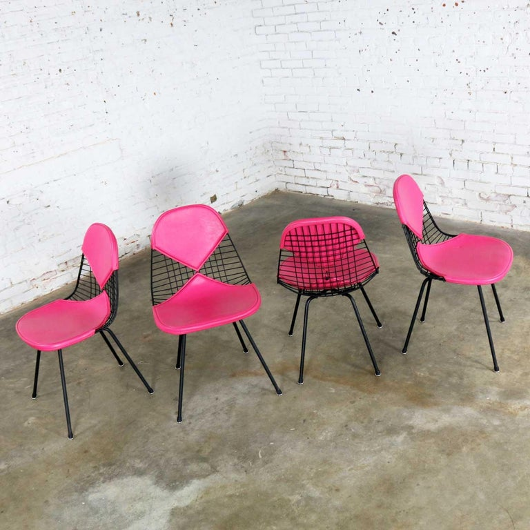 Fabulous set of four DKX-2 wire bikini shell chairs on X bases with Hot Pink Naugahyde bikini covers designed by Charles and Ray Eames for Herman Miller. They are in wonderful vintage restored condition overall. The chairs have had some factory weld