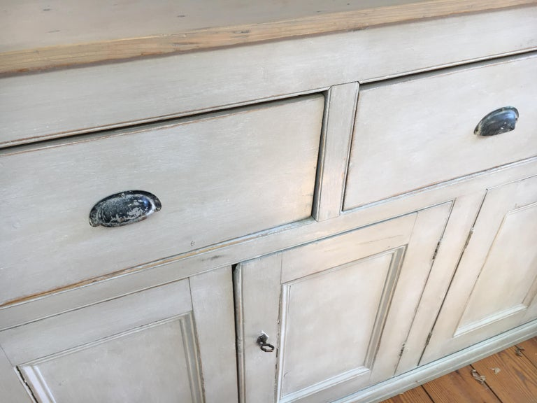 A gorgeous light grey painted base with a light scrubbed pine top and metal pulls, combined with 2 locks and keys. If that weren't enough there is much storage space available inside with shelves. A really, really good looking piece