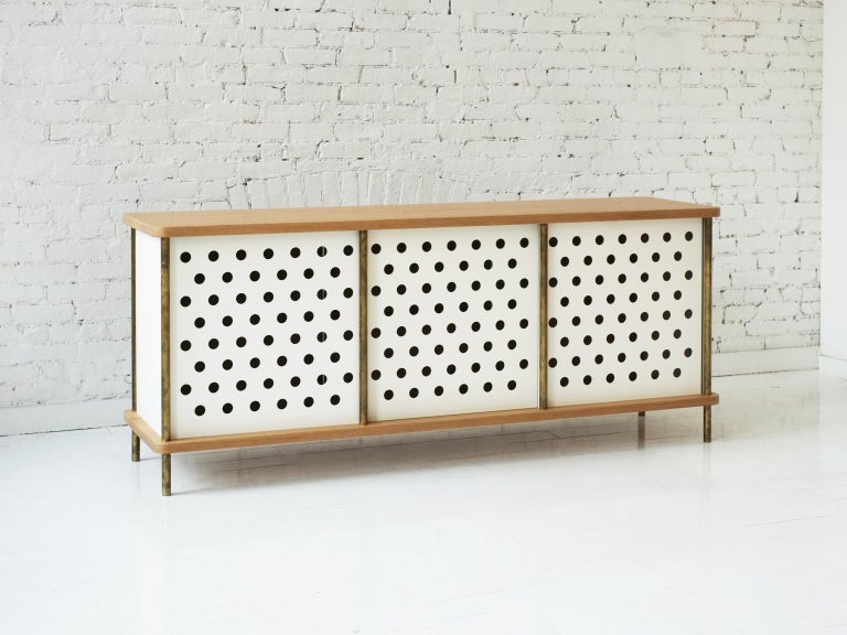 Consistent with the Strata collection, the new Strata credenza is designed to be modular in order to create versatile configurations tailored to your needs. Immediately available as shown with brass rods, walnut top and four powder coated aluminum