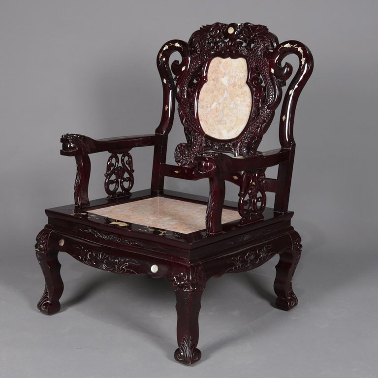A set of four figural Chinese armchairs features inset marble seats with backs framed in dragons and having flanking scroll form supports with mother of pearl inlay featuring foliate elements surmounting hardwood base having carved foliate skirt and