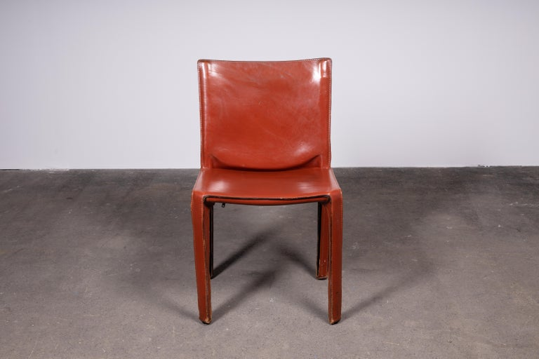 Two sets of two (or one set of 4) cognac Mario Bellini cab 412 chairs, made by Cassina in the 1980s. Flexible steel frame covered with a skin of high quality cognac saddle leather. This elegant, versatile chair is equally suitable for the dining