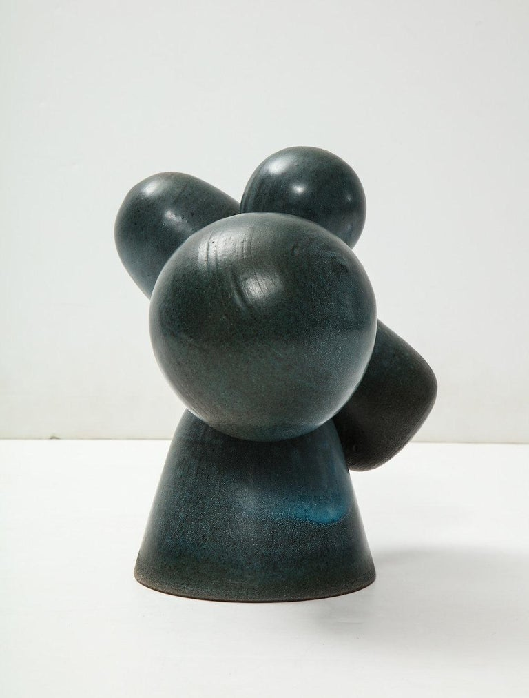Cylindrical and spherical wheel-thrown forms floating on a central rounded cone base. Dark teal glazes. Artist-signed to underside.