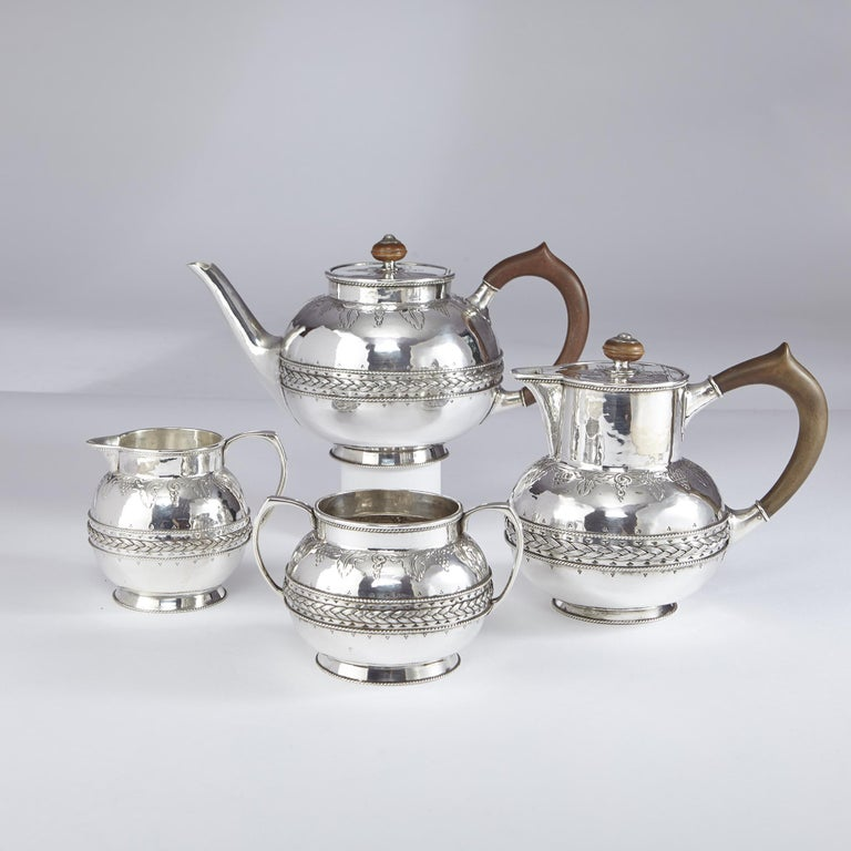 A hand-raised and hand-chased four-piece silver tea set, comprising a teapot, hot water jug, sugar bowl and milk jug. Each piece reflects its Arts & Crafts heritage with finely detailed cast and applied girdles of woven wirework patterns set against