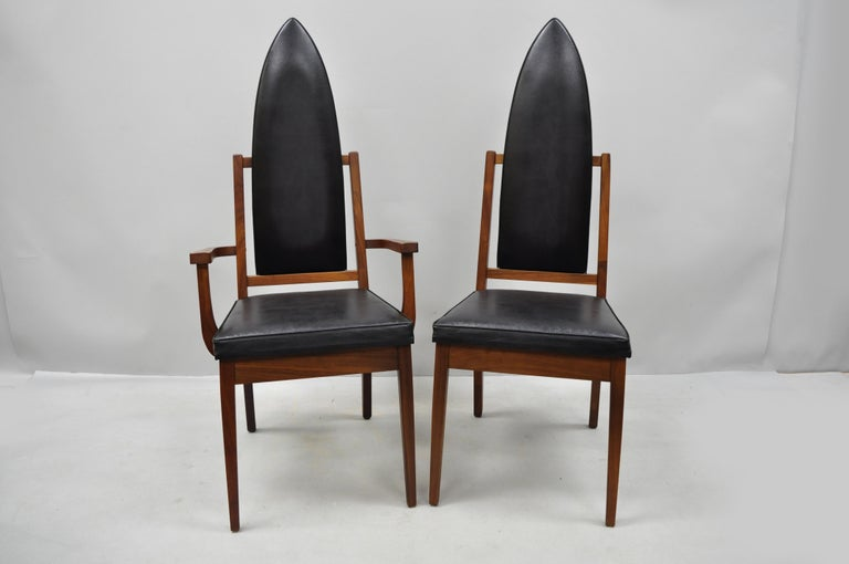 Set of four tall point back walnut Mid-Century Modern dining chairs after Adrian Pearsall. Listing includes 2 armchairs, 2 side chairs, solid wood construction, beautiful wood grain, black vinyl upholstery, tapered legs, sleek sculptural form, circa