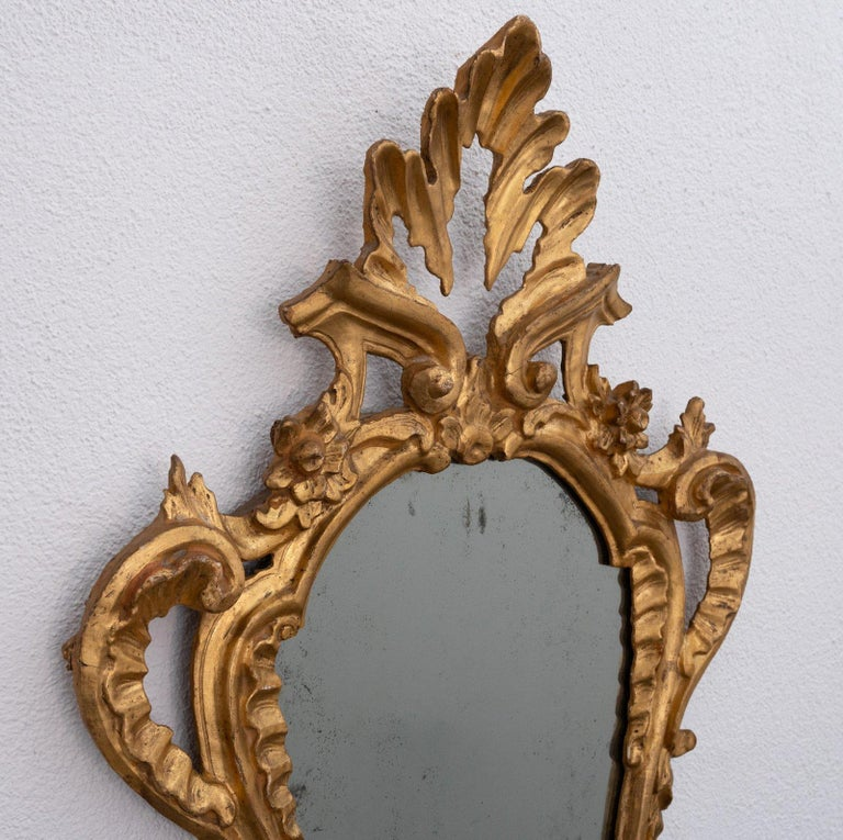 Set of four Italian carved giltwood girandoles, probably Tuscan, Italy circa 1800 priced for the four. Several repairs, oxidation to the mirror plates, sconces lacking.