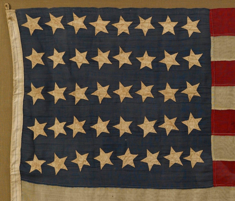 This 40-star American flag is very rare and celebrates the addition of North and South Dakota to the Union.   The body of the flag is constructed of wool, with 40 machine-sewn, double-applique cotton stars configured in 8/8/8/8/8 horizontal rows.