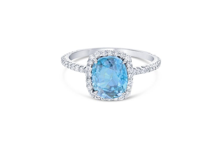 A Dazzling Blue Zircon and Diamond Ring! Blue Zircon is a natural stone mined in different parts of the world, mainly Sri Lanka, Myanmar, and Australia.   This Cushion Cut Blue Zircon is 3.45 Carats surrounded by a simple halo and shank of 68 Round