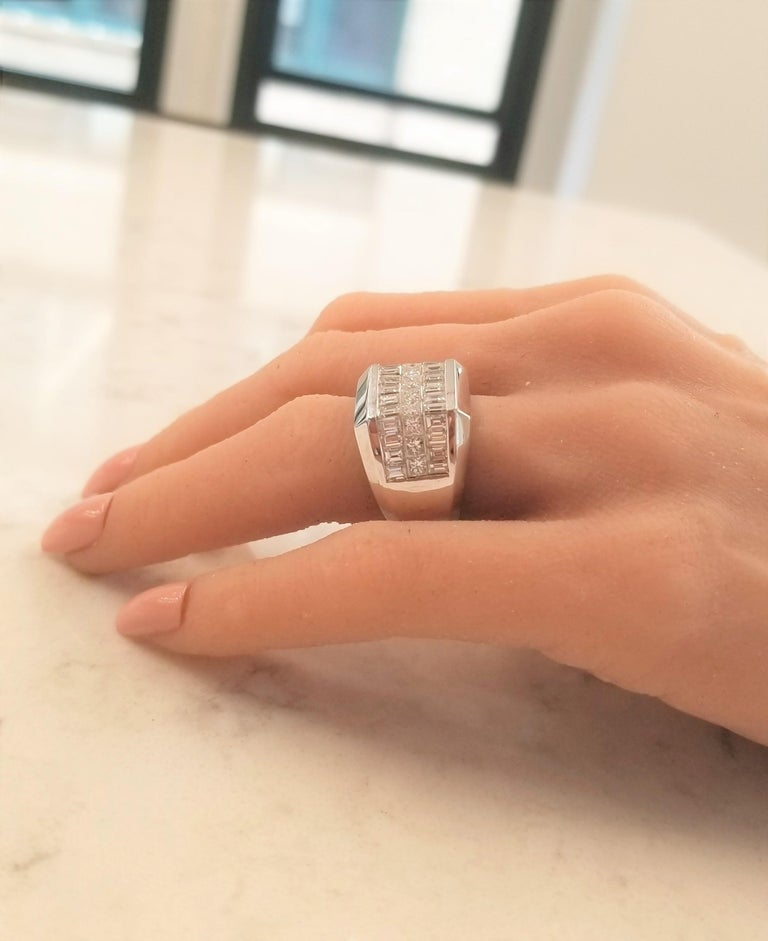 What's not to love about this handsome men's ring? It is bold. It is masculine. It is outstanding! Set in luxurious 18 Karat white gold, this ring features 3 rows of invisible set diamonds that all exhibit F-G color and VS clarity. The first row is