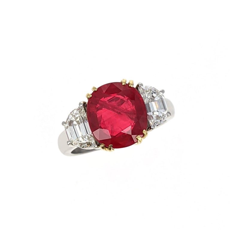 This beautiful ring centers upon an oval-shaped ruby weighing 4.07 carats and is flanked by two half moon-shaped diamonds. It is mounted in platinum and yellow gold. Size 5.5.  Accompanied by a report from the AGL laboratory stating that the ruby is