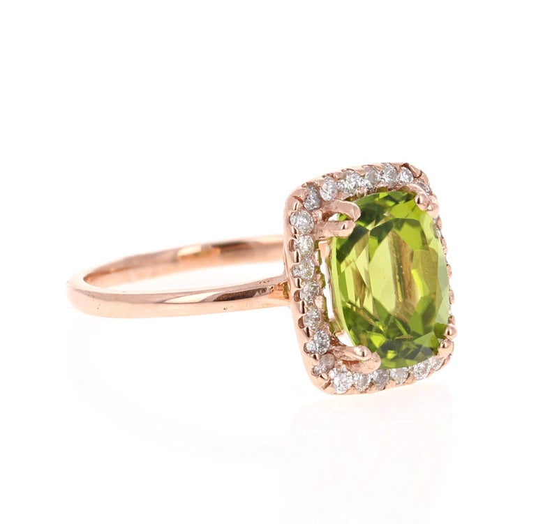 Bright, Beautiful and Bling!   This Peridot and Diamond Ring has a 3.70 Carat Cushion Cut Peridot and has a halo of 26 Round Cut Diamonds weighing 0.37 Carats. The total carat weight of the ring is 4.07 Carats.   It is set in 14 Karat Rose Gold and