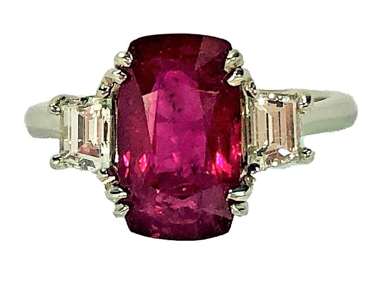 This lovely, elongated, cushion shaped Ruby is set with one brilliant trapezoid diamond flanked on each side. The Ruby weighs 4.07CT but looks and spreads more like a  5CT stone. The Ruby has been certified by AGL (Document #1091034) as a natural