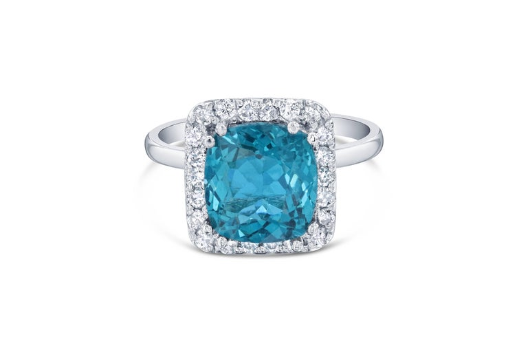 Gorgeous Halo Apatite and Diamond Ring.  This ring has a 3.71 carat cushion cut Apatite in the center of the ring and is surrounded by 22 Round Cut Diamonds that weigh 0.41 carat Clarity: SI2, Color:F.  The total carat weight of the ring is 4.12