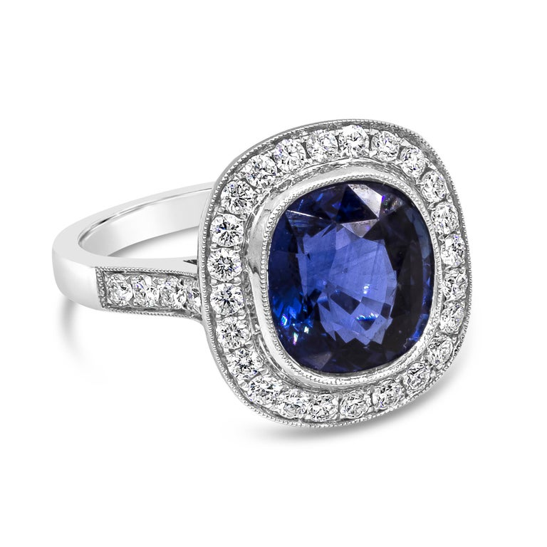 A vintage-style engagement ring showcasing a 4.12 carat cushion cut blue sapphire, surrounded by a single row of round brilliant diamonds. Set in an 18 karat white gold mounting accented with diamonds. Finished with milgrain design on the edges for
