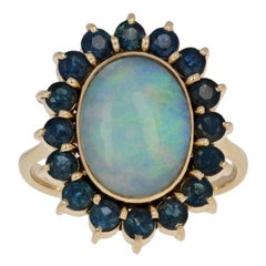 4.13 Carat Oval Cabochon Cut Opal and Sapphire Ring, 18 Karat Yellow Gold Halo