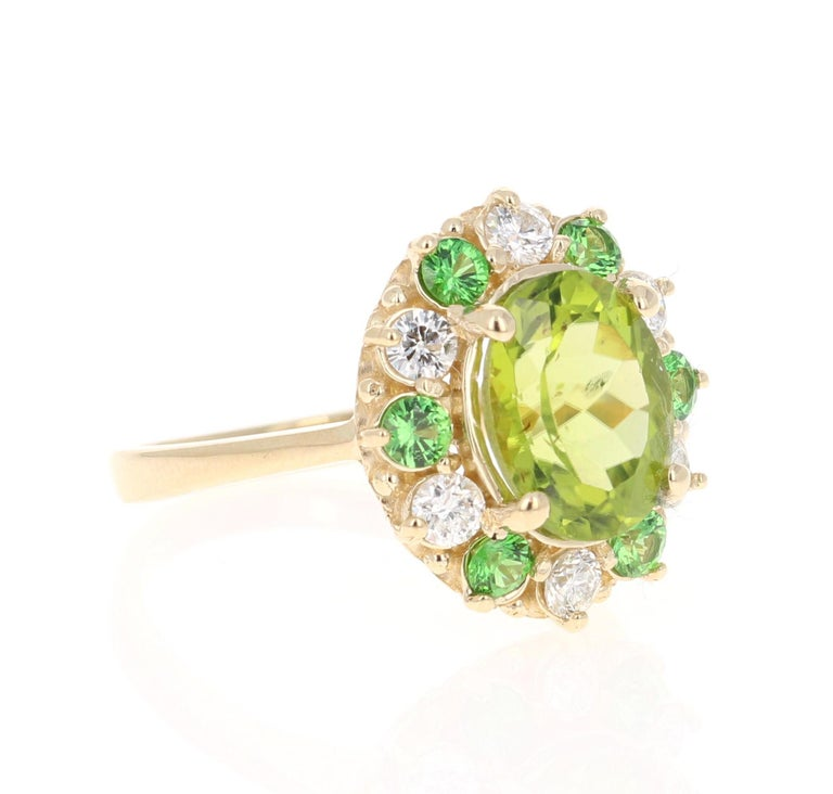 4.13 Carat Peridot Diamond Tsavorite Yellow Gold Ring - this can be a stunning and unique alternative to a unique engagement ring!  This beautiful ring has a Oval Cut Peridot in the center that weighs 3.14 carats. The Peridot measures at 8 mm x 10