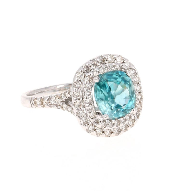 A Dazzling Blue Zircon and Diamond Ring! Blue Zircon is a natural stone mined in different parts of the world, mainly Sri Lanka, Myanmar, and Australia.   This Oval Cut Blue Zircon is 3.31 carats surrounded by a double halo of 70 Round Cut Diamonds