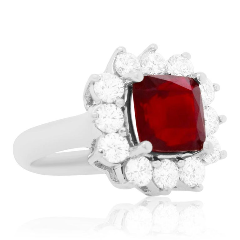 Material: 18K White Gold Gemstone Details: 1 Cushion Ruby at 4.2 Carats- Measuring 8.5 x 8.5 mm  Diamond Details: 12 Brilliant Round White Diamonds at 1.60 Carats. SI Clarity / H-I Color.  Ring Size: 6.75. Alberto offers complimentary sizing on all