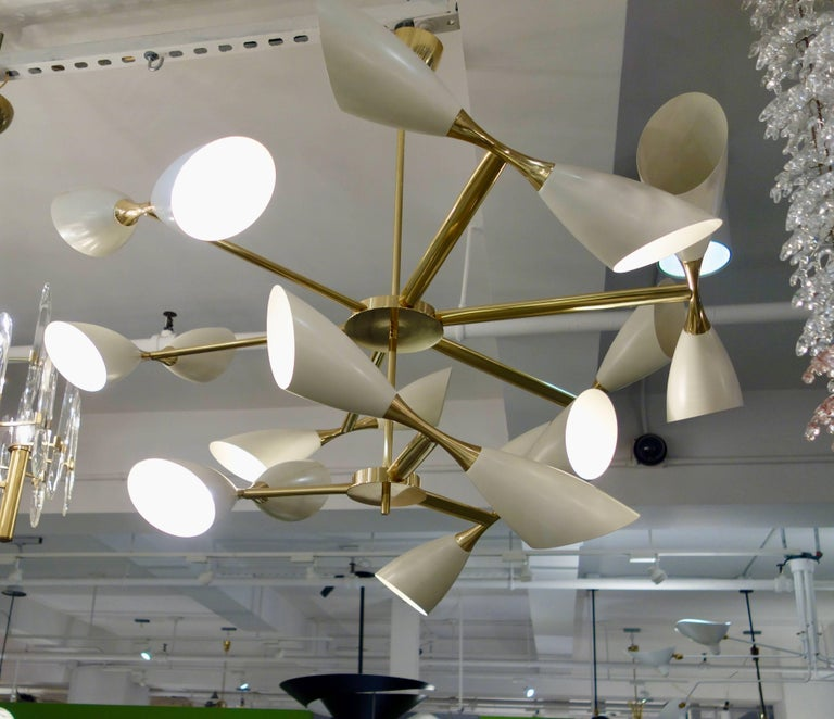 """A 42"""" Italian midcentury style cream lacquer and solid brass studio made chandelier featuring two tiers with a total of nine arms, each with two cream colored shaped cones on each end of a brass rod suspended from a central pole with matching"""
