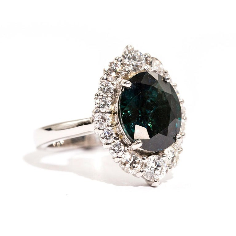 Forged in platinum is this wondrous ring that features a breath-taking 4.25 carat oval natural sapphire of a strong deep teal (blue green) colour complimented with an alluring border of total of 1.16 carats of sparkling round brilliant cut diamonds.