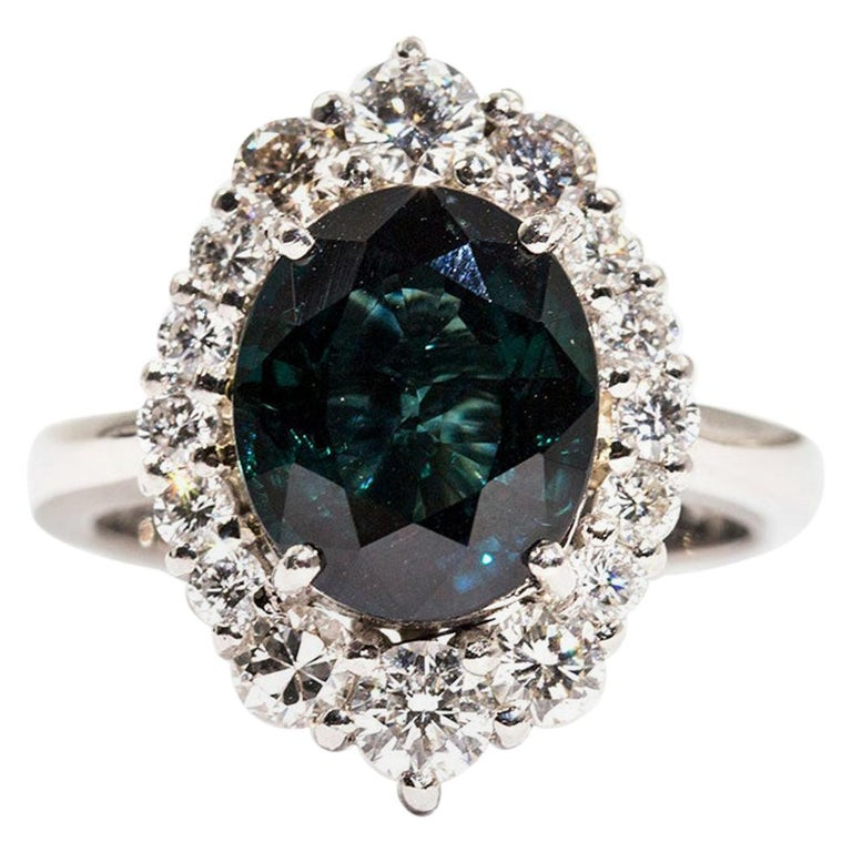4.25 Carat Oval Teal Colour Sapphire and 1.16 Carat Diamond Halo Platinum Ring For Sale