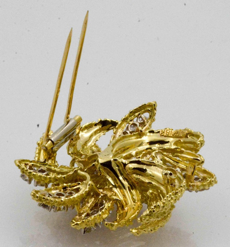 This extraordinary brooch of 18 karat yellow gold impresses with an intricate leaf pattern that that twists and turns with elegance. 35 round brilliant cut diamonds weighing 4.27 carats (G-H color, VS internal clarity) have been exquisitely set in