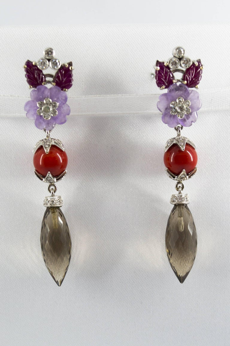 These Earrings are made of 18K White Gold. These Earrings have 1.10 Carats of White Diamonds. These Earrings have 4.30 Carats of Rubies. These Earrings have also Agate, Bambù Coral and Fume Quartz. All our Earrings have pins for pierced ears but we