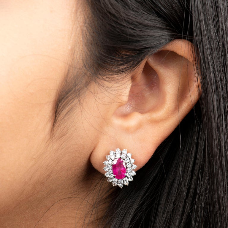 4.32 carat natural oval rubies, likely of Burma origin and no-heat, surrounded by 1.80 carats of fine round brilliant cut diamonds in a double halo design (F-H color & SI-1 to SI-2 clarity). These earrings were designed in 14K white gold with omega