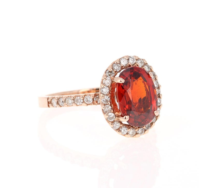 This beautiful ring has a 3.49 carat Oval Cut Spessartine set in the center of the ring. A Spessartine is a natural stone that is actually a part of the Garnet family of stones. The ring is surrounded by 32 Round Cut Diamonds that weigh 0.38 carat.