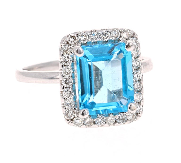 This stunning statement ring has a large Emerald Cut Blue Topaz that weighs 3.94 Carats.  It is surrounded by a simple halo of 26 Round Cut Diamonds that weigh 0.41 Carats.   It is crafted in 14 Karat White Gold and weighs approximately 3.7 grams.