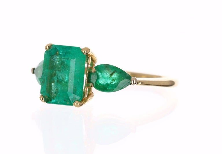 Setting: Three-Stone Metal Purity: 18K Yellow Gold Weight: 4.9 grams  Center Stone: Emerald Shape: Emerald Cut Approx Weight: 3.35-carats Clarity: Semi-Transparent Color: Green Luster: Excellent-Very Good Origin: Colombia Treatments: Natural,