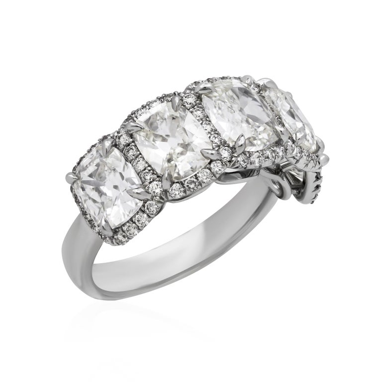 Features 5 cushion cut diamonds weighing 4.38 carat total and accented by a row of round brilliant diamonds weighing 0.54 carat total. Set in 18K white gold. Size 6 1/2 US (sizable).  Style available in different price ranges. Prices are based on