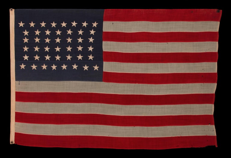 44 Star Flag With Beautifully Hand-sewn Stars In An Hourglass Pattern On A Soldier Blue Canton, An Antique Example; Reflects The Addition Of Wyoming 1890-1896  44 star antique American flag of the late 19th century. The stars are hand-sewn, made