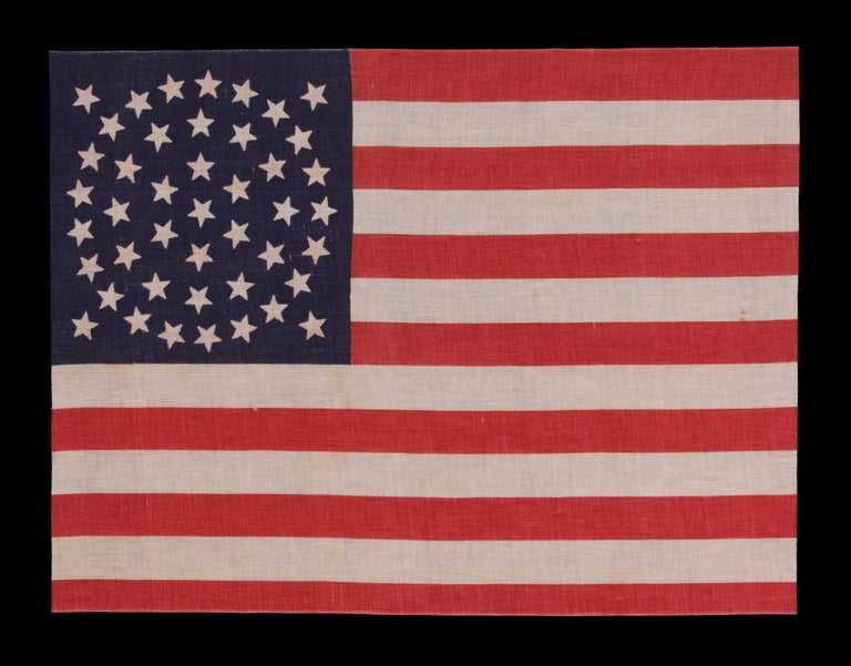 44 Stars on a Large Scale Parade Flag, Wyoming Statehood, 1890-1896, Rare in this Period with a Wreath Configuration  44 star American parade flag with triple wreath medallion star configuration, printed on cotton. This highly desired star pattern
