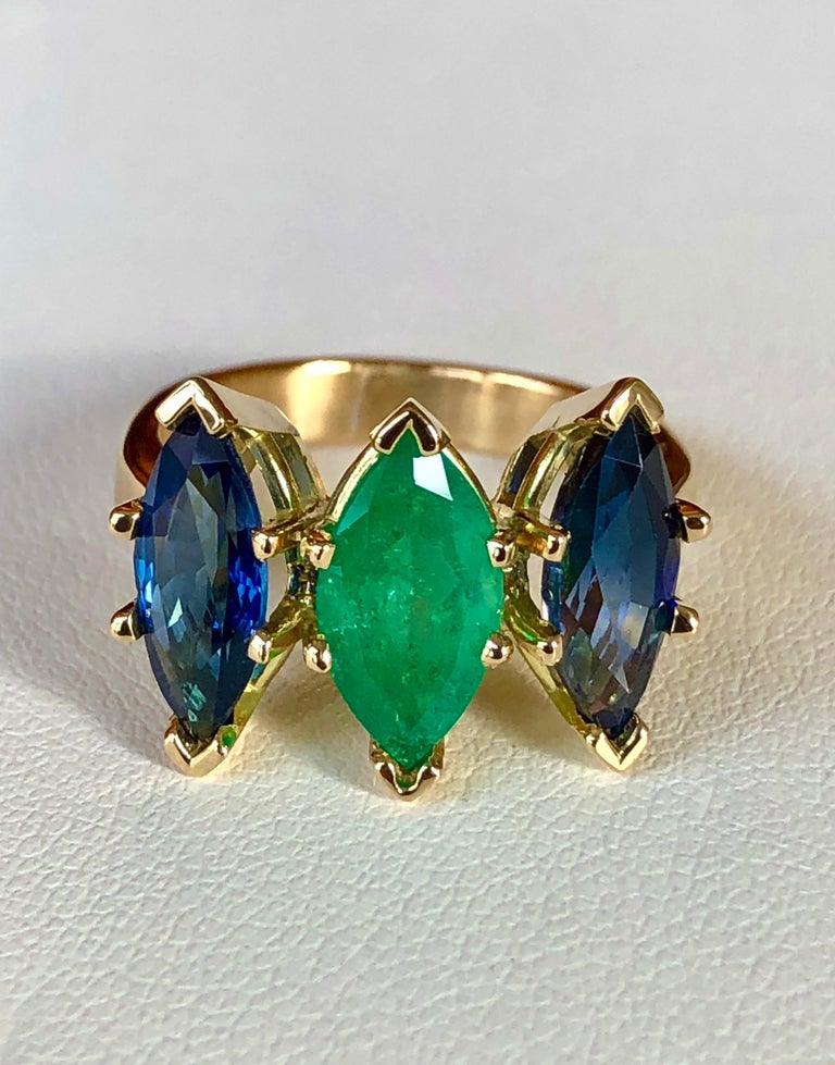 A SUPER RARE Find for this unique three stone ring features a center one marquise cut bright green natural Colombian emerald 1.38 carat , surrounded by two natural Ceylon sapphires marquise cut totaling 3.06 carat. The stones are carefully matched