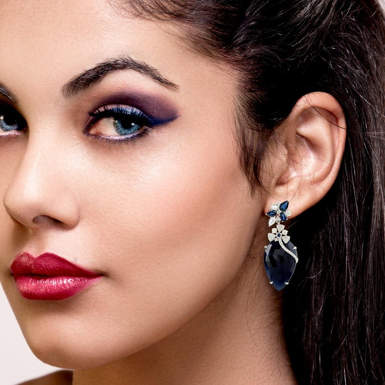 Cast in 18-karat gold, these stunning drop earrings are hand set with 44.43 carats blue sapphire and 1.6 carats of sparkling diamonds.   FOLLOW  MEGHNA JEWELS storefront to view the latest collection & exclusive pieces.  Meghna Jewels is proudly