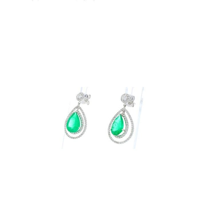 Gorgeous 4.45 carat total mint green, pear cut emeralds sit front and center of these spectacular earrings. The emeralds are vivid and perfectly matched, originating from Zambia. The quality is gem-quality providing excellent luster. The gemstones
