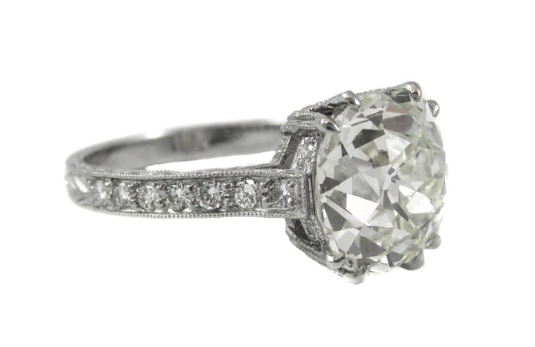 Exquisitely hand crafted platinum mounting with detailed engraving around the shank. Fine bright white and sparkling round brilliant cut diamonds are set along each shank with miligrain work on either side of the platinum walls. Centrally set in