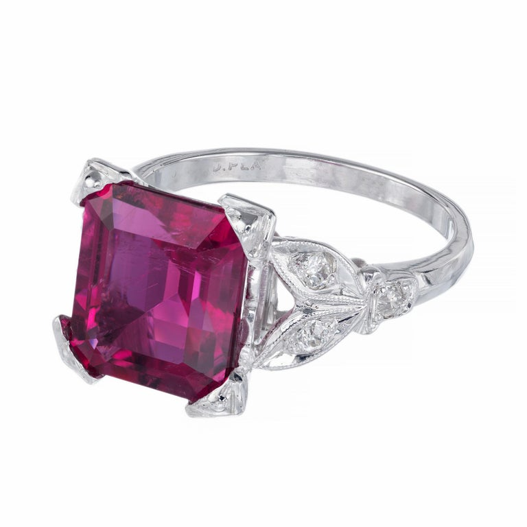 Bright red rubellite tourmaline and diamond Art Deco ring. 4.49ct emerald cut center stone with 6 round old European cut accent diamonds in a platinum setting from teh 1920's.   1 reddish pink rectangular step cut rubellite tourmaline, approx.
