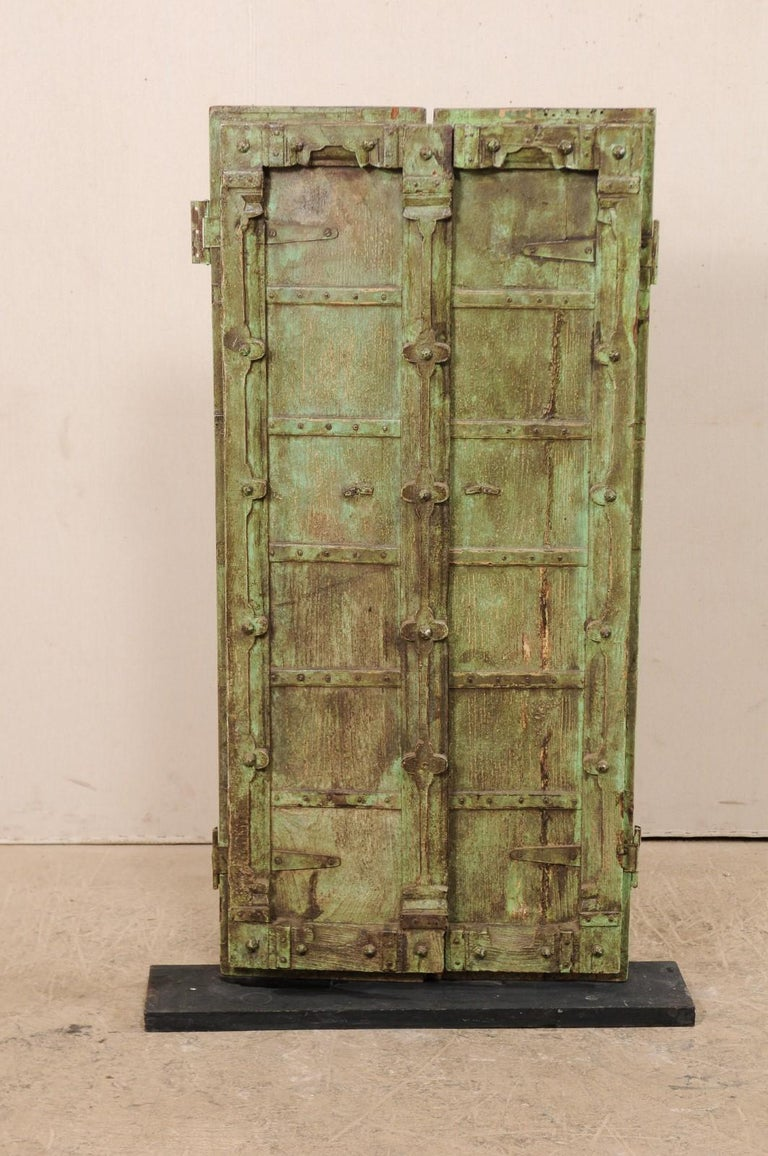 A short pair of Indian doors from the turn of the 19th and 20th centuries presented upon a custom Stand. This antique pair of doors each feature six vertically square panels, with sweetly carved flower motifs down the center where they meet as well
