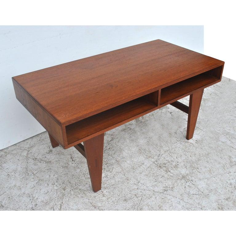 Vintage midcentury coffee table   Teak with tapered legs   Open shelf area. Measures: 45