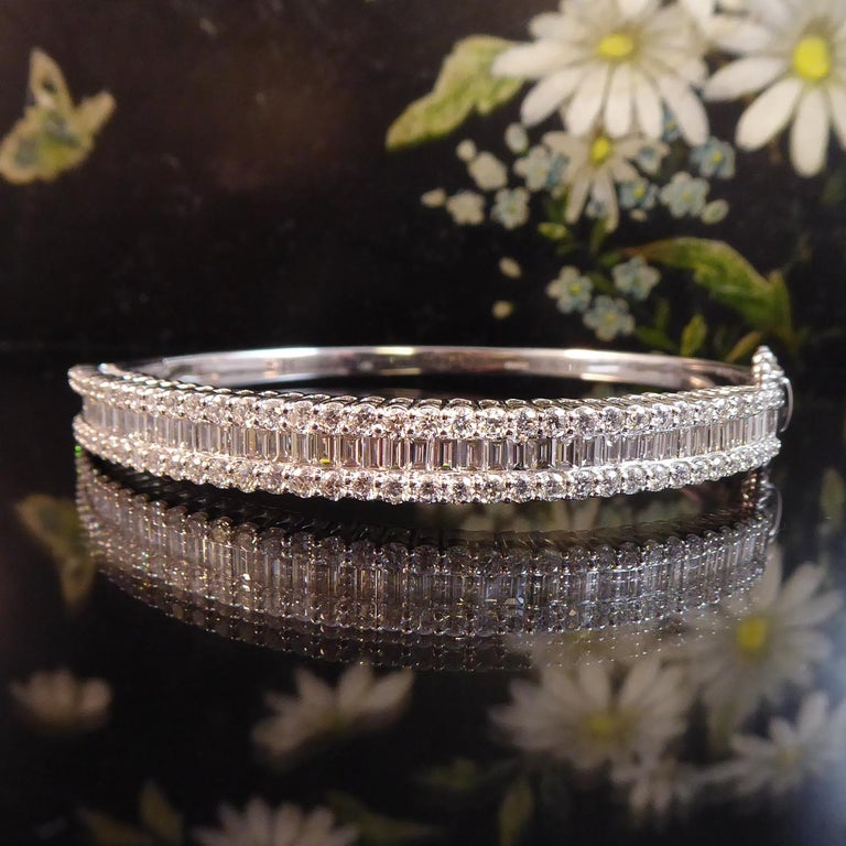 New and unworn this spectacular diamond bangle boasts 4.51ct of diamonds in total.  The centre of the bangle is set with a row of 49 baguette cut diamonds, totalling 2.17ct  in a channel setting.  To each side of this baguette section is a row of