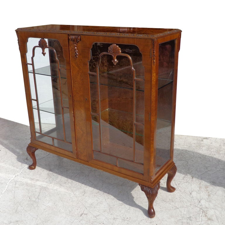 Art Deco Display Curio cabinet Pratts of Bradford  Beautiful burled walnut with double doors opening to 2 glass shelves. Carved cabriole legs with decorative appliques on doors. Measure: 45.5
