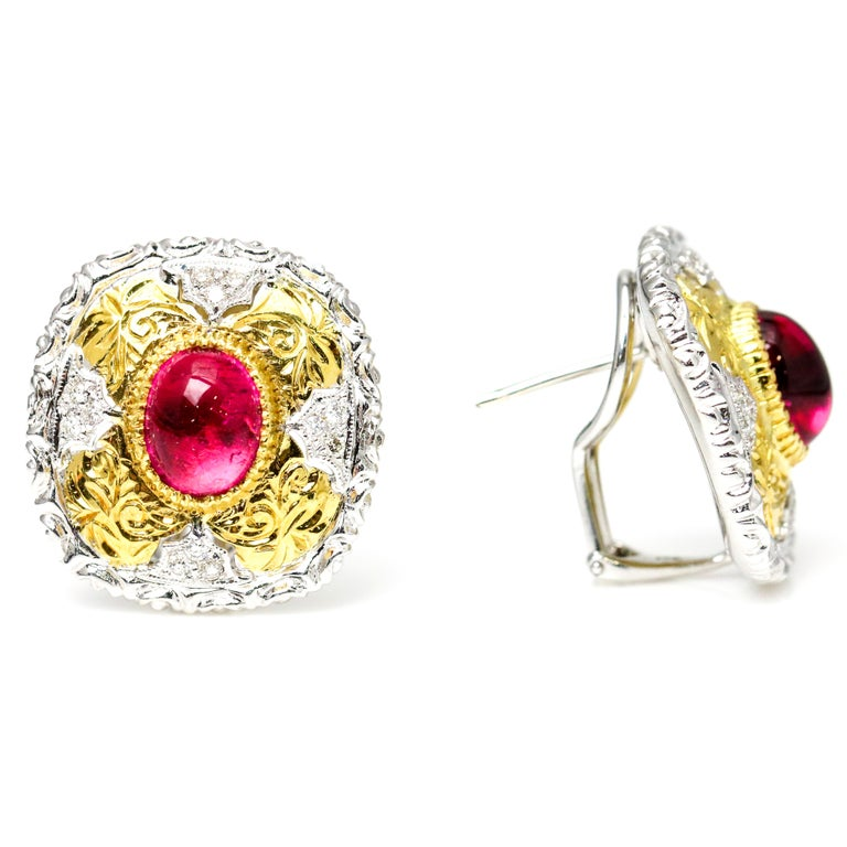 Large square stud earrings crafted in 18 karat white and yellow gold bezel set with a cabochon-cut pink tourmaline and prong set with diamonds. The earrings have intricate gold work throughout that enhances the vibrant pink tourmaline gemstone at