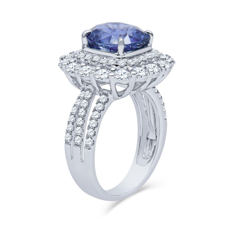 4.57 Carat total cushion cut Ceylon natural, heat only, blue sapphire (AGL report) with 1.93 carats total weight in round brilliant natural diamonds set in a double halo setting 18K white gold ring. This is a highly sought after 'cornflower' blue