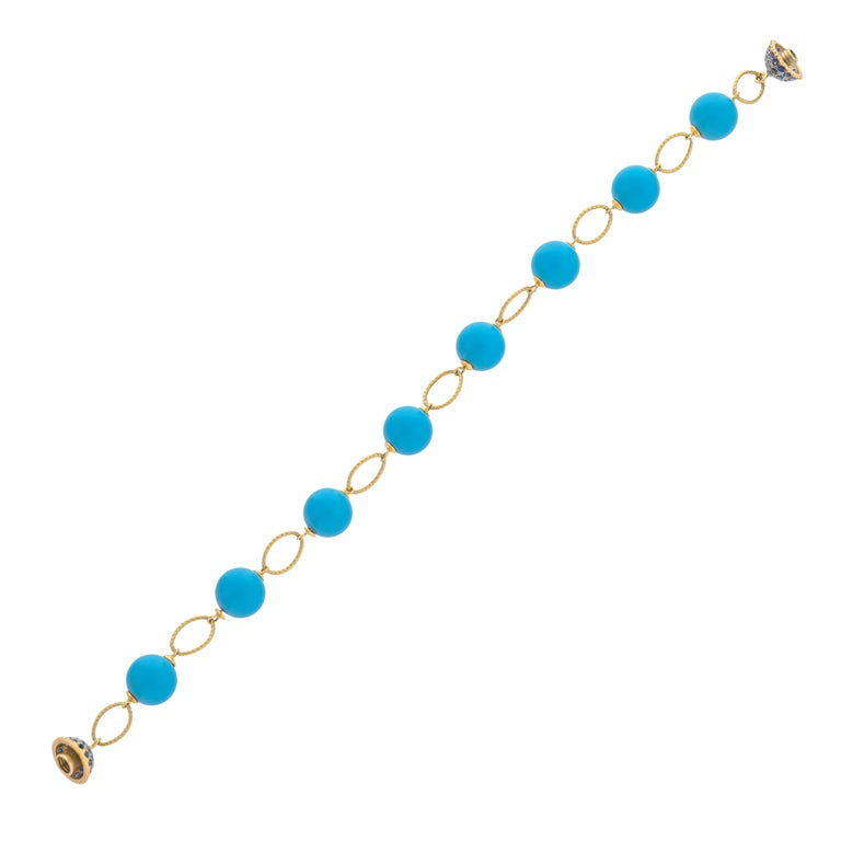 45.71 carats turquoise make such a simple but fashionable bracelet further enhanced with 18 karats yellow gold link and 1.16 carats blue sapphire ball lock, this is 'haute couture'. Gemstone size- turquoise -  10x10mm Length of bracelet - 8.50