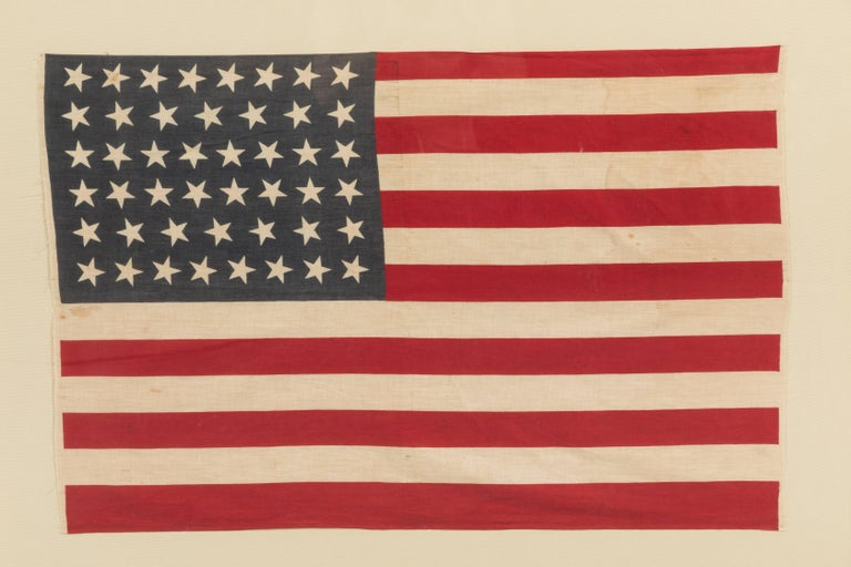 46 Star flag printed on cotton muslin. Linear arranged stars in rows of 8, 7, 8, 8, 7, 8. Oklahoma was the 46th state and gained statehood on November 16, 1907. The 46 star flag was the official American flag from July 4, 1908 to July 3, 1912. Acid