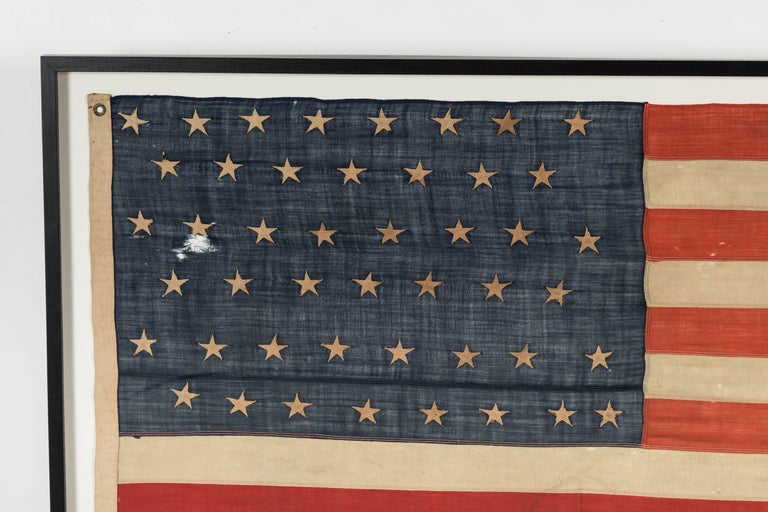 Nice large scale framed American 46 star flag. Hand-stitched and randomly applied folk art stars. The rest of the flag construction is machine stitched. Exact measurements are 86.5 wide by 46